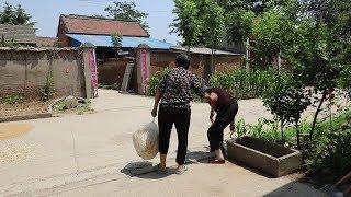 农村婆媳门口干活,遇见老街坊来买东西,婆婆小跑掂一大兜送给她