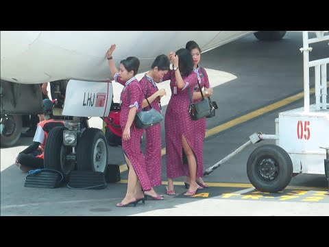 Pramugari Lion Air berteduh di Bawa Pesawat Menunggu Penumpang Turun di Bandara Ngurah Rai Bali