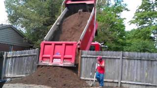 Tri axle of dirt getting dumped