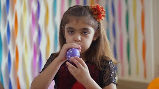 Cute little girl blowing purple balloon with white dots - Birthday party decoration