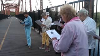 People singing to the harvest moon on the Fair Oaks pedestrian bridge.