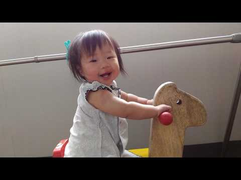 One year old baby is riding the wooden horse.