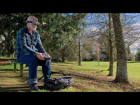 Old man walks, talks and flies a drone in the park