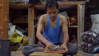 Professional local craftsman making Indian traditional footwear for women