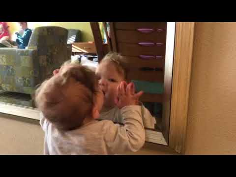 Baby girl talks to herself in the mirror