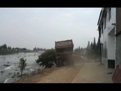 Trucks Carrying Rocks Driven into Flood to Block Dyke Breach in Hunan