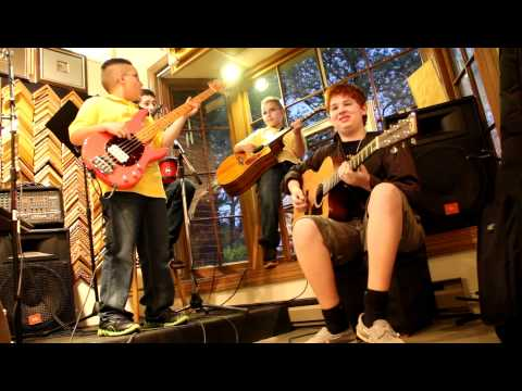 Kid band plays Running With The Devil.  Van Halen cover.