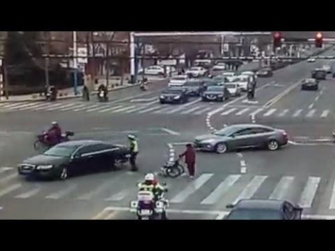 Shandong Province: Two police officers escort a senior citizen across road