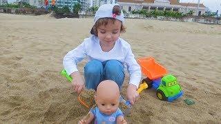 Makar juega con una muñeca en la playa. Formación de color con Caja de arena