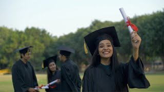 Attractive Indian graduate posing towards the camera with a big smile on her face