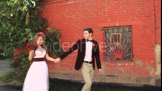 Bride and Groom Walking Along a Brick Red Wall