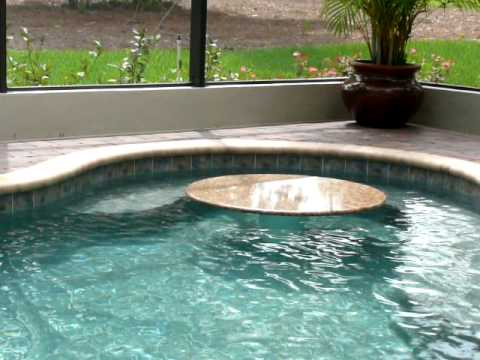 swimming pool featuring a rock waterfall and a marble table with bench seat youtube