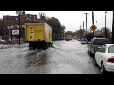 HURRICANE SANDY cars drive into flooded streets in Rockaway N.Y.