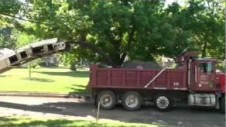 A fleet of dump-trucks and an asphalt grinder working on street...
