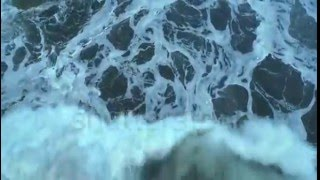 aerial drone footage of textured pattern formed by white sea foam lockdown shot of huge ocean waves