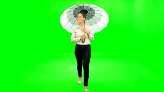 Girl walking with umbrella and enjoying rain against the green screen
