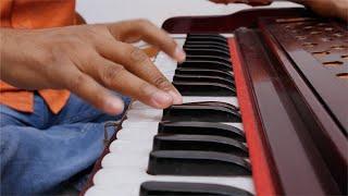 Indian musician playing keyboard of harmonium
