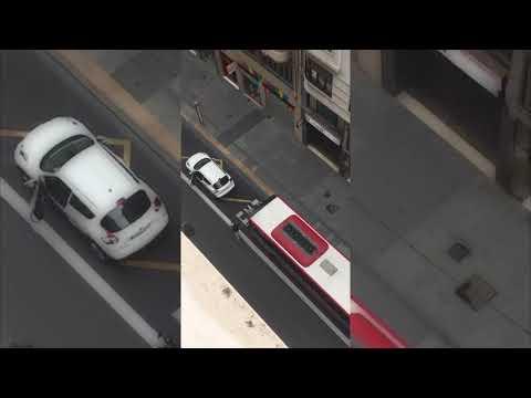 Un autobús empurra un coche parado nun carril bus