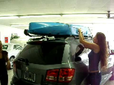 Girls Tying Kayak On Roof Of SUV
