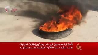 أطفال حلب يحرقون الإطارات لحجب الرؤية عن الطائرات