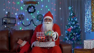 Old Santa sitting on a couch with colorful Christmas presents during Christmas time