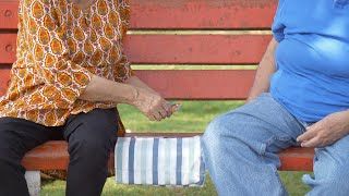 Closeup shot of old man and woman enjoying playing card games in a park