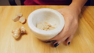 Slow motion of a girl hand pounding ginger in a stone mortar