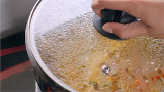 Female opening a glass lid of steel vessel with boiling vegetables