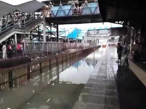 Indian railway train splashing water on platform like roller coaster.  Mumbai monsoon 2017