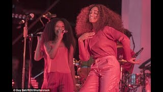 Solange Knowles rocks out in a bright red ensemble at Glastonbury... after welcomes twins