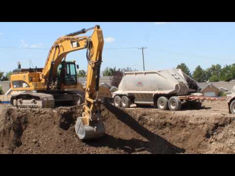 CAT 345D Excavator loading 2 different bottom dumping double big rig dump trucks on a construction s