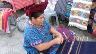 Maya woman in Guatemala creates a hand made blanket and clothing one thread at a time.