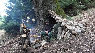 BUSHCRAFT. PRIMITIVE SHELTER MADE OF STONES AND WOOD. FIRE REFLECTOR BUILDING. COOKING OVER THE FIRE