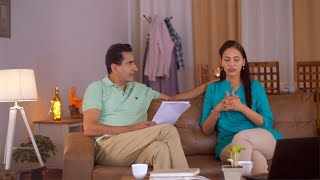 Stressed Indian wife having tea while having a discussion with husband about financial issues