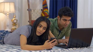 Indian husband working on the laptop while wife busy on phone