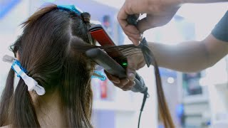 Closeup shot of a girl having her hair straightened by a hairstylist in a hair salon