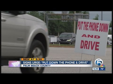 "Signs urge: ""Put Down the Phone and Drive"""