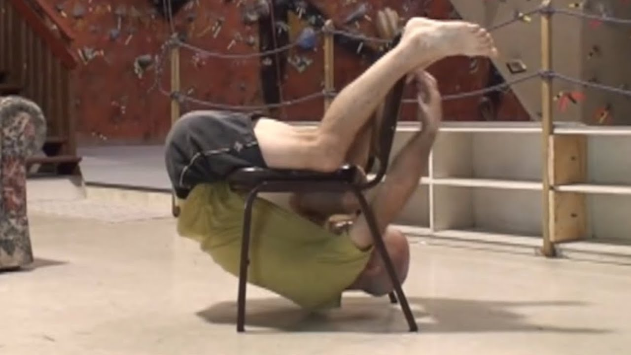 Guy twists around a chair without touching the ground