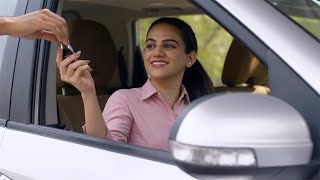 Young business woman taking keys of her brand new car from a salesman