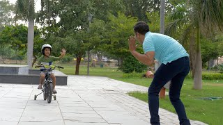Indian father and son happily doing high five while riding a bicycle - Sunday leisure time