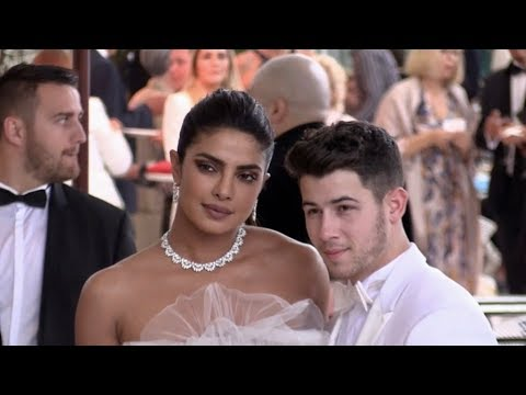 Nick Jonas and Priyanka Chopra dressed up in white as a married couple coming out of the Martinez ho