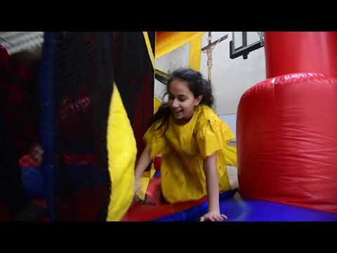 Kids play on inflatables at Queen of the Miraculous Medal School