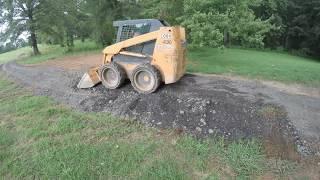 Spreading asphalt millings on a driveway.