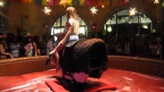 Girl riding a mechanical bull like a boss