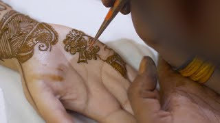 Mehndi artist applying beautiful henna / mehndi of the hands of an Indian bride