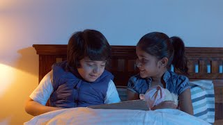 Little Indian kids sitting on the bed - Using touchscreen tablet and watching a movie - Fun and Technology