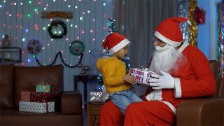 Santa Claus giving a gift box to a cute little boy during Christmas celebration in India