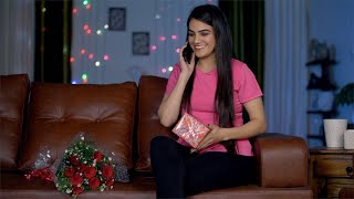 Beautiful smiling female sitting with valentine's day presents and calling her boyfriend