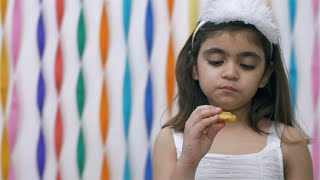 Happy little girl in white dress eating potato smiley fries at a birthday party
