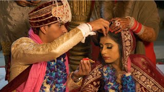 Stock video of an Indian groom putting sindoor / vermilion on beautiful brides forehead